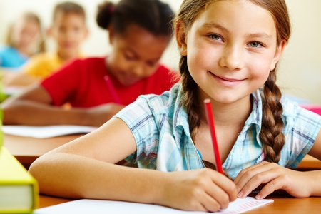 elementary kids: Portrait of lovely girl drawing in copybook and looking at camera