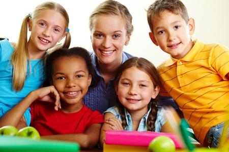 schoolchildren: Portrait of smart schoolchildren and their teacher looking at camera in classroom Stock Photo