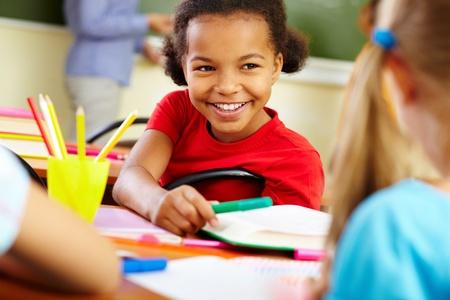 niños en la escuela: Retrato de linda chica dando crayon a classmate en lección Foto de archivo