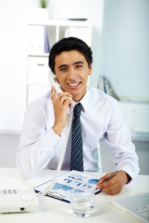 Portrait of a businessman talking on phone in office photo