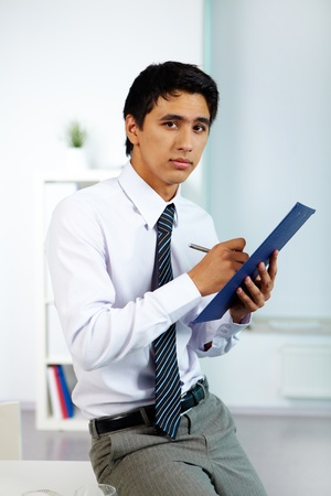 Portrait of a businessman writing plan of work in office photo