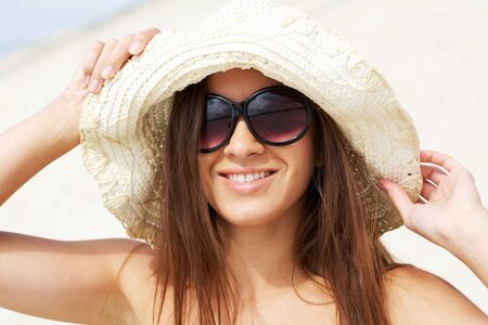 Portrait of pretty young lady in hat touching it and looking at camera through sunglasses Stock Photo - 10446134