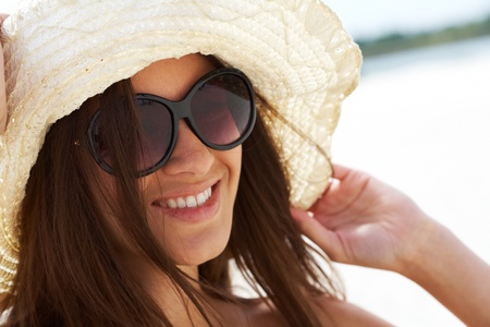 Portrait of pretty young lady in hat looking at camera through sunglasses photo