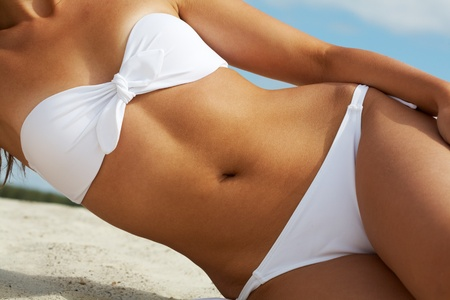 partes del cuerpo humano: Torso de mujer lujosa en bikini blanco tomando el sol Foto de archivo