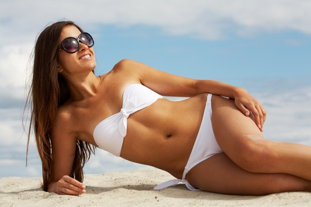 tanned body: Image of female in white bikini sunbathing on sandy beach