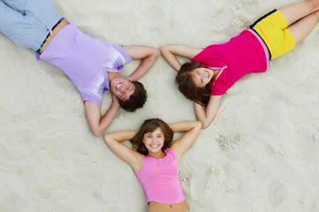 Above angle of happy teenage friends lying on sandy beach photo