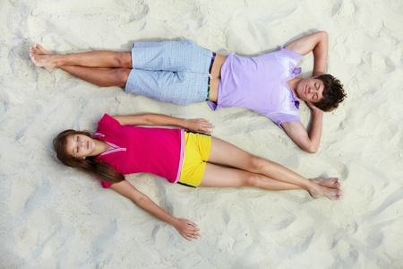 Above angle of two teenage friends having rest on sandy beach photo