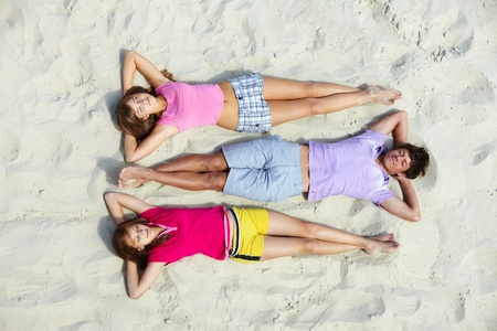 Above angle of relaxed teenage friends lying on sandy beach photo