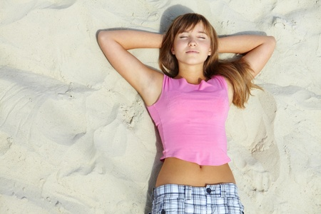 nap: Above angle of pretty teenager lying on sandy beach