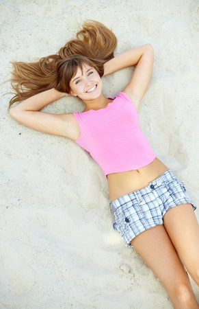 feminine beauty: Above angle of pretty teenager lying on sand and laughing Stock Photo
