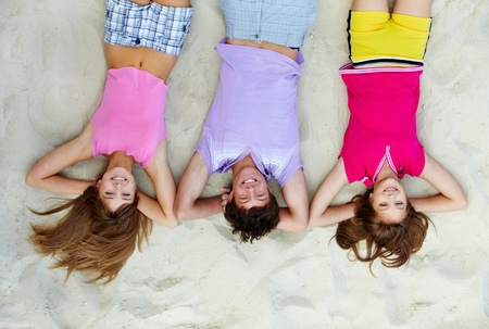 Above angle of laughing teenage friends lying on sandy beach photo