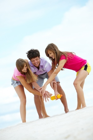 Portrait of laughing teenagers having fun on sandy beach photo
