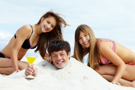 Two girls in bikini and happy guy with cocktail having fun on sandy beach photo