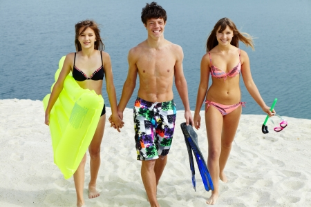 Two girls in bikini and happy guy walking down the beach photo