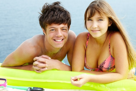 Portrait of teenage girl in bikini and her boyfriend lying on mattress and sunbathing photo