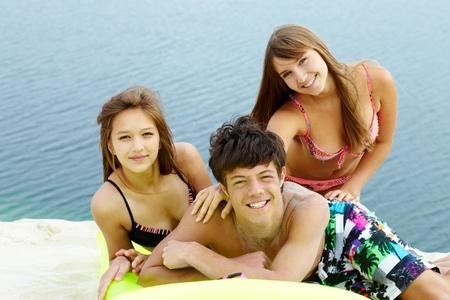 Portrait of three teenage friends spending time by seaside photo