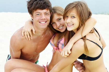 teenage guy: Portrait of happy teenage guy and girl holding their friend
