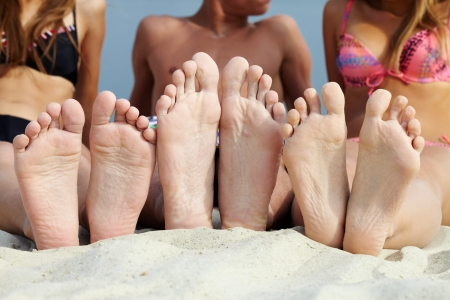 woman foot: Soles of teenagers sunbathing on sandy beach