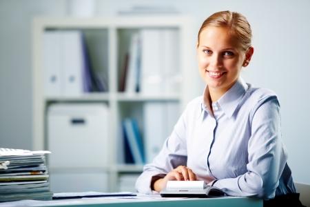 Retrato de una empresaria joven feliz mirando a la cámara en la oficina