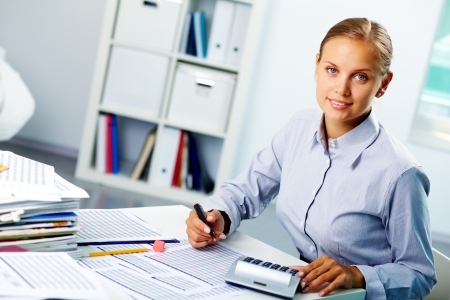 economist: Portrait of a young happy businesswoman looking at camera while working in office