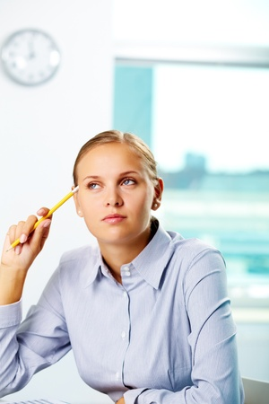 economist: Portrait of a young businesswoman thinking at work Stock Photo