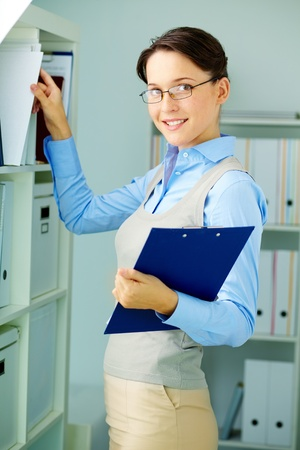 secretaria: Retrato de mujer de negocios elegante, con prestigio portapapeles estantería en la oficina Foto de archivo