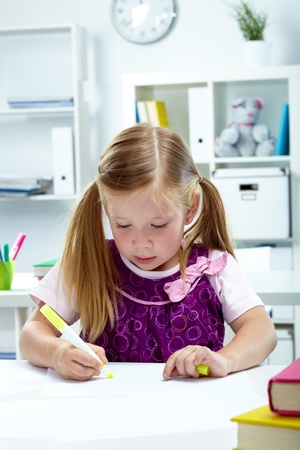Portrait of lovely girl drawing with yellow highlighter photo