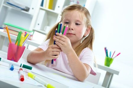 artworks: Portrait of lovely girl with colorful crayons looking at them Stock Photo