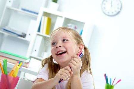 Portrait of joyful girl with colorful crayons photo