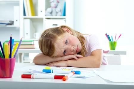 verdrietig meisje: Portret van trieste meisje dat haar hoofd op het bureau Stockfoto