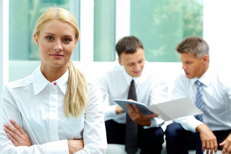 foreground: Confident businesswoman looking at camera at background of communicating men Stock Photo