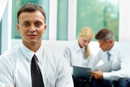 Confident businessman looking at camera at background of his communicating colleagues Stock Photo - 10503889