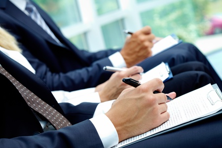 executive courses: Close-up of business people hands with papers writing at lecture  Stock Photo
