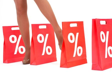 Legs of lady standing between red paper bags photo