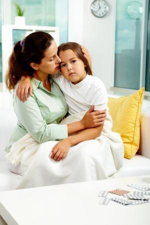 krankes kind: Portrait of vorsichtig Female h�lt ihre Kranken Tochter beide sitzen auf sofa