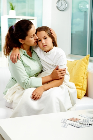 sick kid: Retrato de mujer cuidadosa sostiene a su hija enferma mientras tanto sentado en el sof�