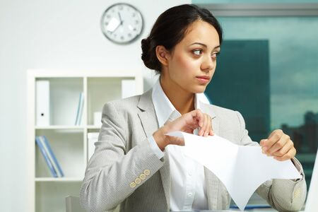 Image of young employer tearing paper with troubled expression photo