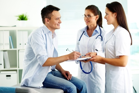 happy patient: Portrait of confident female doctors and happy patient in hospital Stock Photo
