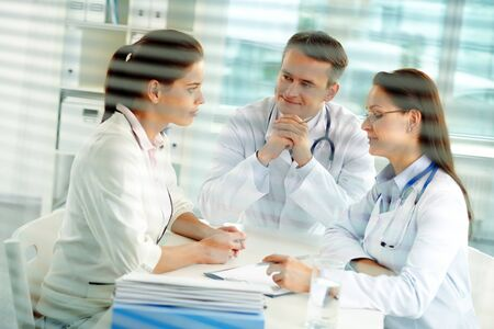 Portrait of confident practitioners consulting patient in hospital Stock Photo - 10546455