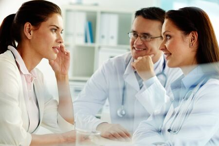 Portrait of confident practitioners consulting patient in hospital Stock Photo - 10546645