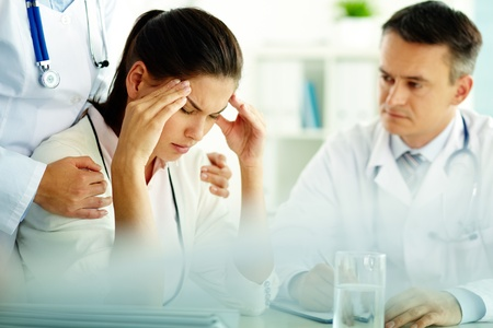 dolor de cabeza: Retrato de mujer con dolor de cabeza toca las sienes con el personal m�dico cerca