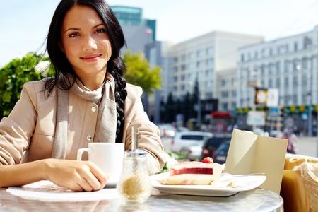 wealthy lifestyle: Immagine di felice femmina in caffetteria all'aperto guardando fotocamera in ambiente urbano