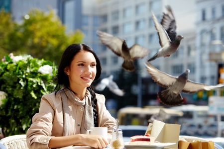 white pigeon: Image of happy female in open air cafe having coffee with cake in urban environment Stock Photo