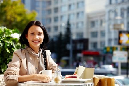 wealthy lifestyle: Immagine di felice femmina in caffetteria all'aperto guardando la fotocamera in ambiente urbano
