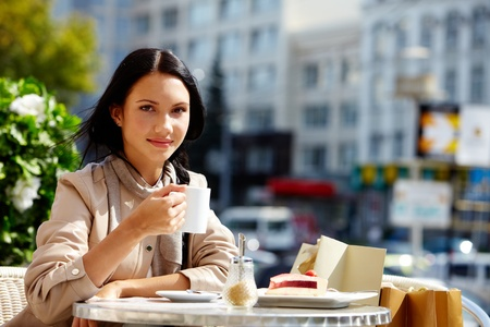 open air: Image of young brunette in open air cafe looking at camera in urban environment
