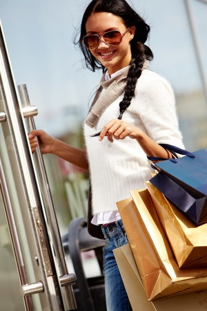 paperbags: Image of happy female with paperbags opening the door of department store in urban environment Stock Photo