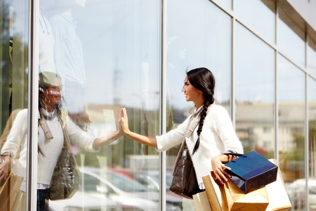 Image of happy female with paperbags touching and looking at shop window in urban environment photo