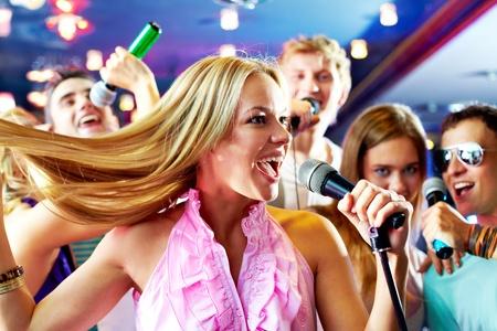 persona cantando: Retrato de ni�a cantando alegre en la fiesta en el fondo de amigos felices