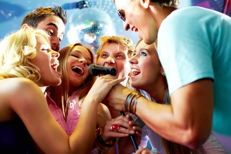 karaoke: Portrait of joyous guys and girls singing at party in one microphone