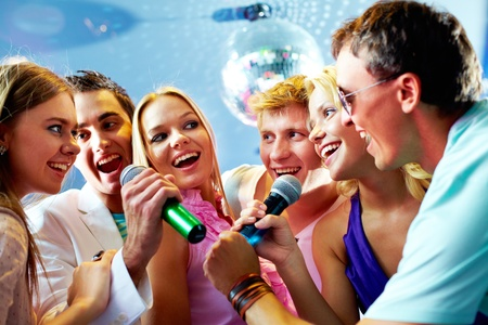 joyous: Portrait of joyous guys and girls singing at party together